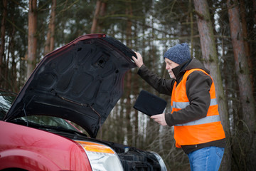 man driver wearing a high visibility vest  bending over the engine of his broken down car during winter time