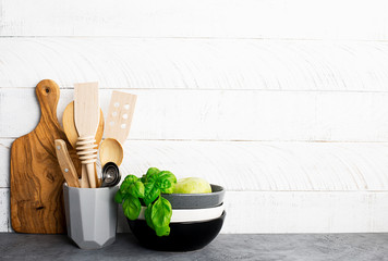 Kitchen shelf with appliances and cutlery against a white wooden wall. Horizontal. Copy space. No plastic concept.