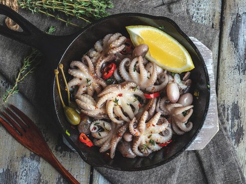 Baby octopus cooked, roasted in the iron pan portion, with lemon and seasoning close up