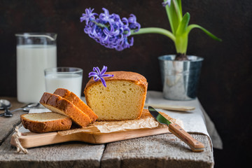 Tasty homemade traditional cake with a glass of milk, blue hyacinth potted on wooden baclground