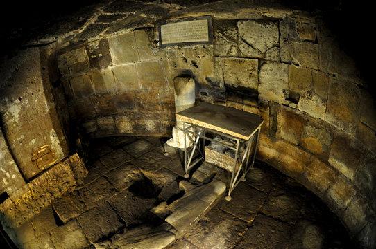 dimly lit ancient roman prison cell