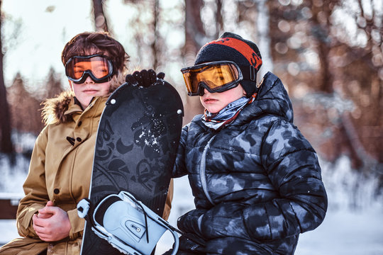 Two teenage brothers dressed in warm clothes sitting on a bench with a snowboard in a forest park