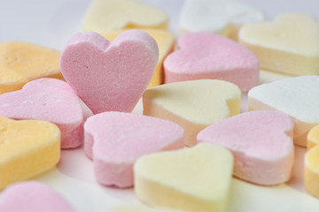 macro color photo of candy hearts lying on white background, one pink heart is standing, copy space