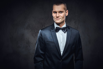 Portrait of a handsome stylish wearing elegant classical suit with a bow tie. Studio shot on a dark textured wall