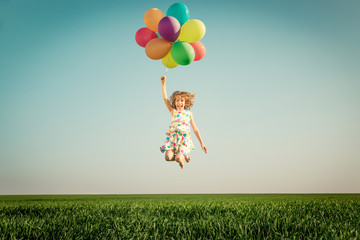 Happy child playing outdoors in spring field