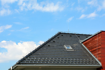 Shingles roof with skylights windows and rain gutter on the background of blue sky. Brick house with lightning conductor.