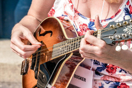 Female musician playing a mandolin, street performer, busker.