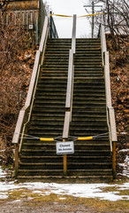 An outdoor weather-worn wooden staircase thas is closed, no access sign, inclement weather, yellow tape, caution.