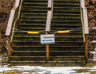 An outdoor weather-worn wooden staircase thas is closed, no access sign, during inclement weather, danger.