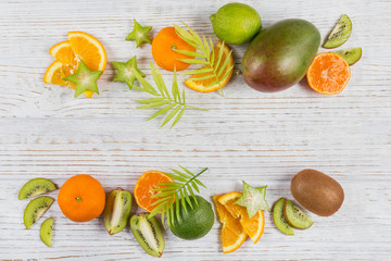 Green palm leaves and fresh tropical slices of fruits