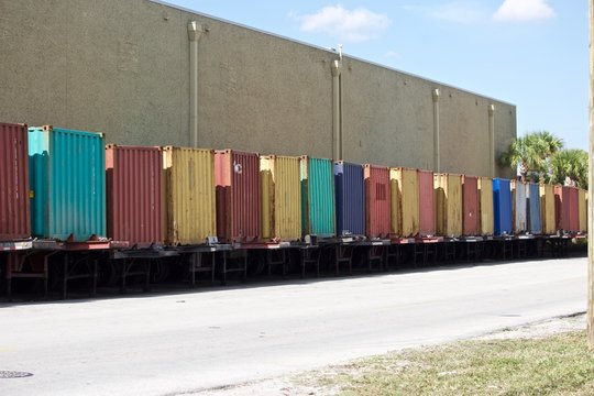 Shipping containers on trailers, colorful row of shipping containers lined up against building