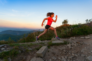 Woman cross country running in mountains at summer