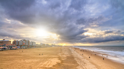Beautiful seaside landscape - view of the beach near the embankment of The Hague with people making promenade, the Netherlands Wall mural