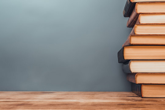 stack of books on a wooden table.
