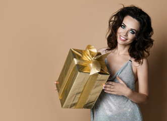 Sensual woman with gold present gift box for birthday party smiling