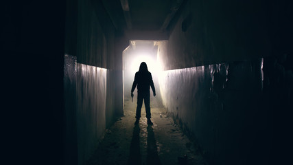 Silhouette of man in dark creepy and spooky corridor