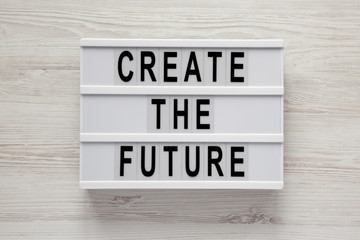 'Create the future' word on lightbox on a white wooden background, top view. From above, flat lay, overhead.
