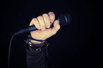 Man hand holding microphone. Leather  bracelet and accessory .Hard rock, heavy metal,gothic and punk style.Brutal jacket