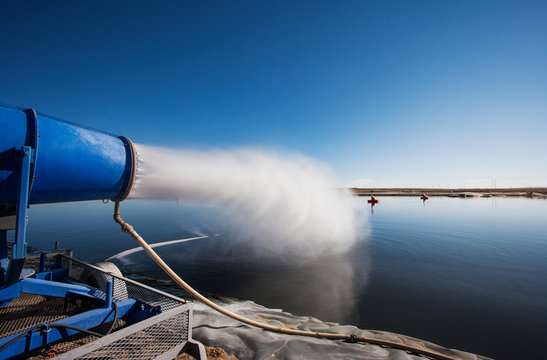 Machine spraying water in lake against clear sky