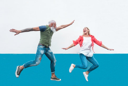 Happy seniors crazy couple jumping together outdoor - Mature trendy people having fun celebrating and dancing outside - Concept of happiness, freedom, carefree, love and relationship
