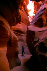 Impressed young traveler woman looking up inside of the Antelope Canyon, Arizona, USA.