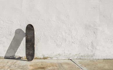 Skateboard on deteriorated white wall during a sunny afternoon with big copy space. Skateboarding background, street sport.