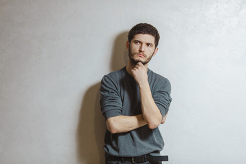 Portrait of young pensive man having new idea, over white textured background.