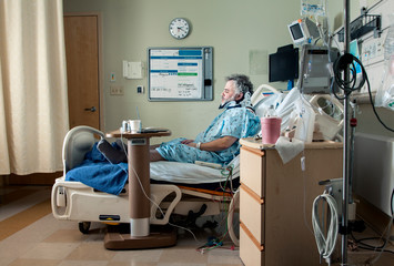 Side view of man sitting on bed in hospital