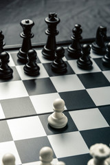 Chess board with black and white chess facing each other. White pawn goes on the attack
