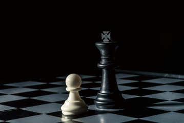 Chess board. Black king threatens white opponent's pawn