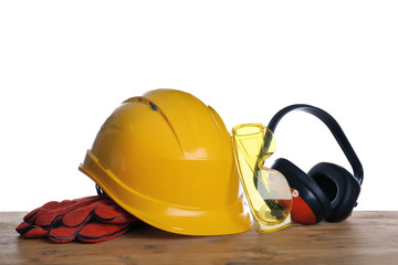 Set of safety equipment on table against white background