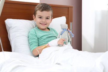 Little child with intravenous drip and toy in hospital bed
