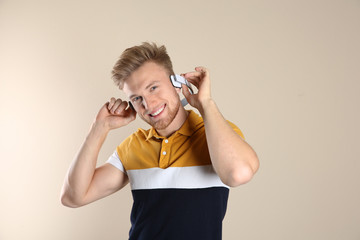 Handsome young man listening to music with headphones on color background