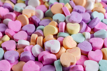 An assortment of conversation hearts top side view.  Pastel colors.  With messages.
