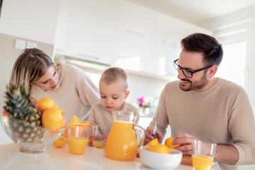 Family make fresh orange juice