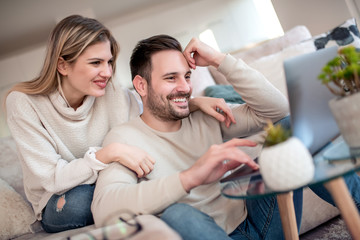 Couple searching something on laptop at home