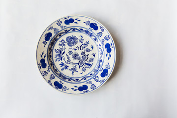 a white round plate with floral and line pattern on white background