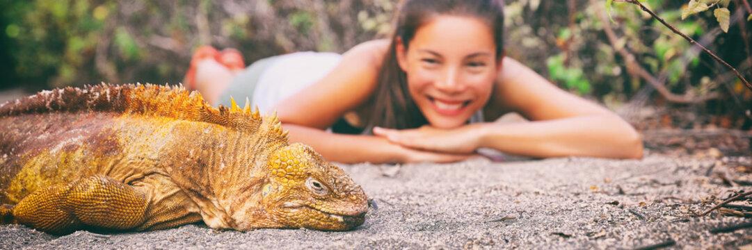 Galapagos islands tourist woman at yellow land iguana on Urbina Bay sand beach panoramic banner. Asian happy girl traveling in Ecuador.