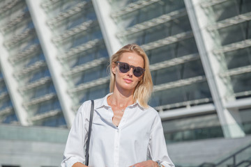Business woman in a white shirt crossed her arms over her chest against of modern building