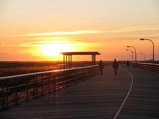An orange and yellow sunset at Jones Beach boardwalk in Long Island, New York.