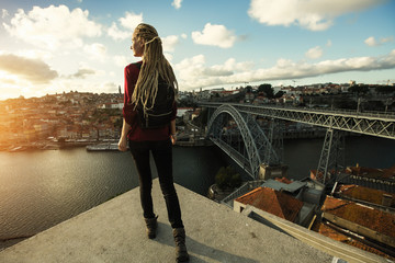 Young woman meets sunset opposite the Dom Luis I bridge and Douro river in Porto - Portugal.