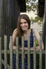 Young woman with long hair near the wooden fences.
