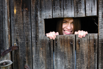 Portrait of young woman looks and smiles out the little window in the wooden shed.