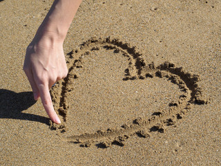 heart drawing a finger in the sand.