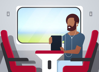 man train passenger listening audio book with headphones african american guy sitting red armchair railway traveling concept male character portrait horizontal