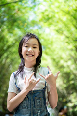 Portrait of smiling little asian girl right sign language meaning I Love You and look at the camera on bamboo forest,green nature background,happy people concept