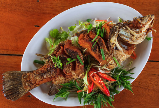 Whole fried fish spicy served with sliced fresh chili peppers, green onions and basil served in a restaurant in Krabi, Thailand