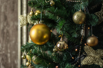 New Year's greased spruce is decorated with golden decorative balls and accessories