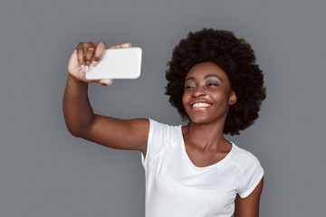 Young woman standing isolated on gray taking selfie on smartphone looking camera laughing cheerful
