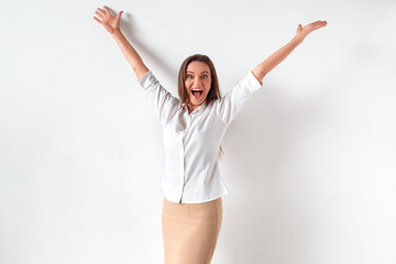 Success achieved. Woman standing isolated on white hands up shouting cheerful